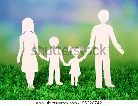 Family from paper on grass on bright background - stock photo