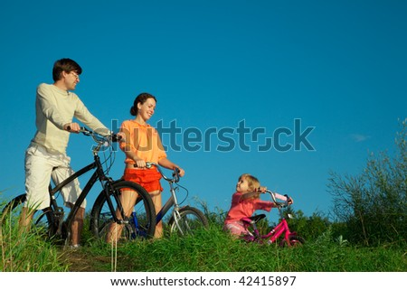 Family from three persons on bicycles. Parents look at a daughter. - stock photo