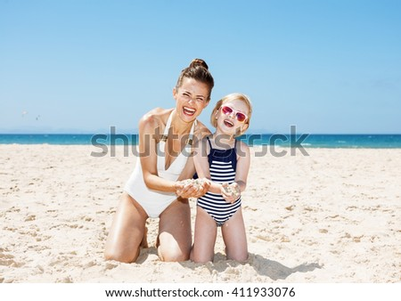 Family fun on white sand. Happy mother and child in swimsuits at beach on a sunny day showing hands full of sand - stock photo