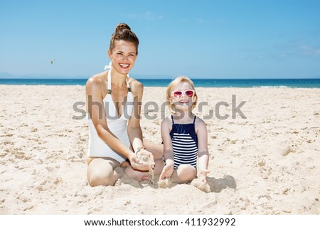 Family fun on white sand. Happy mother and girl in swimsuits at beach on a sunny day playing with sand - stock photo
