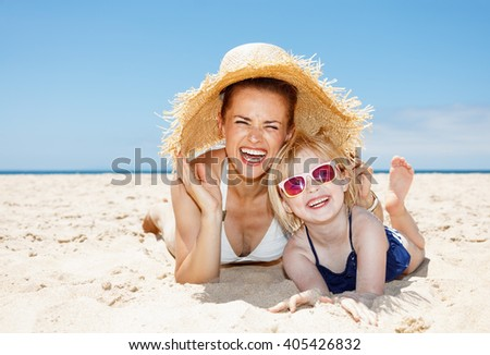 Family fun on white sand. Portrait of smiling mother and daughter in swimsuits laying on sandy beach on a sunny day under big straw hat