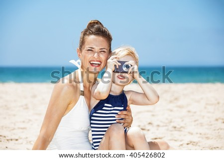 Family fun on white sand. Smiling mother and child in swimsuits taking photos with digital camera at sandy beach on a sunny day - stock photo