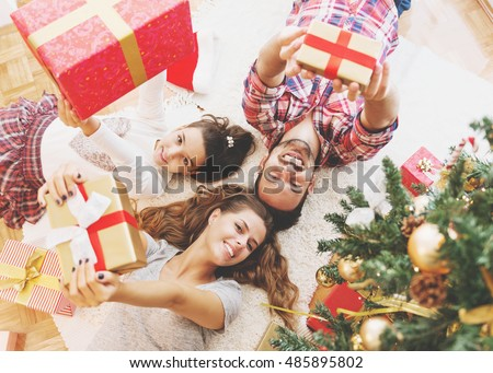 Family gather around a Christmas tree, holding presents