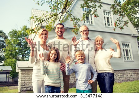 family, generation, gesture, home and people concept - happy family standing in front of house waving hands outdoors