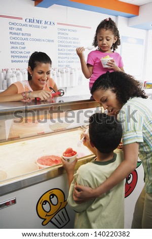 Family getting ice cream in ice cream shop - stock photo