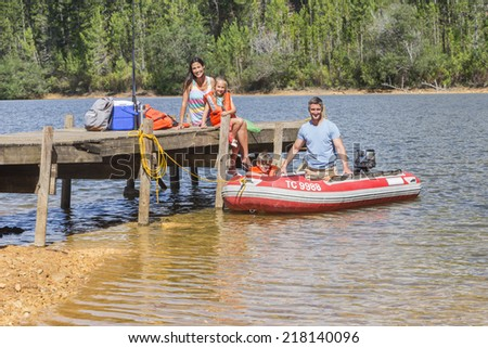 Family Getting Into Inflatable Boat For Fishing Trip - stock photo