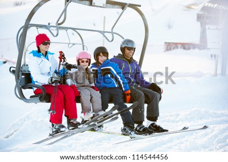 Family Getting Off chair Lift On Ski Holiday In Mountains