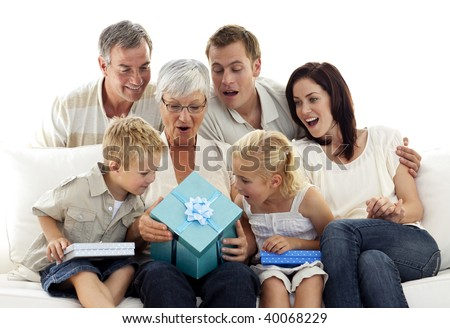 Family giving a present to grandmother for her birthday - stock photo