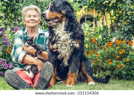 Family. Grandmother sitting in the garden with a cat in his hands and sitting next Mountain Dog. Grandma smiled sweetly dog. Overall plan. - stock photo