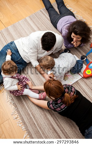 family group of five - two babies and three adults lying on the carpet, playing together.