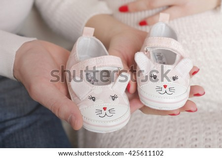 Family Hands, Mother and Father Hand Holding Pink Newborn Baby Booties, New Born Girl - stock photo