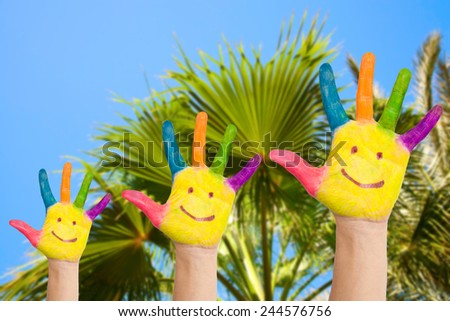 Family hands with smiles against palm and  blue sky background. Summer holidays concept