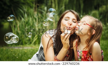Family happiness and carefree concept. Mother and daughter little girl having fun blowing soap bubbles together in park, green blurred background - stock photo