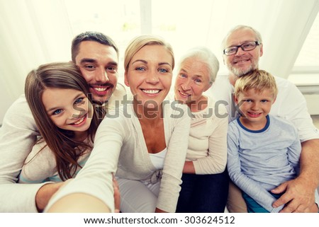 family, happiness, generation and people concept - happy family sitting on couch and making self portrait with camera or smartphone at home - stock photo