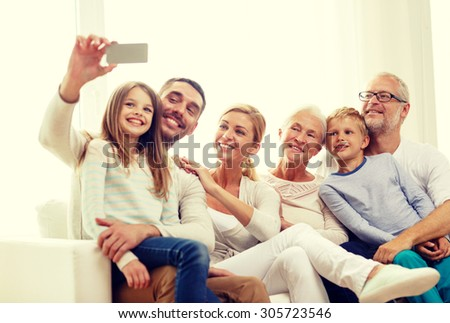 family, happiness, generation and people concept - happy family sitting on couch and making selfie with smartphone at home
