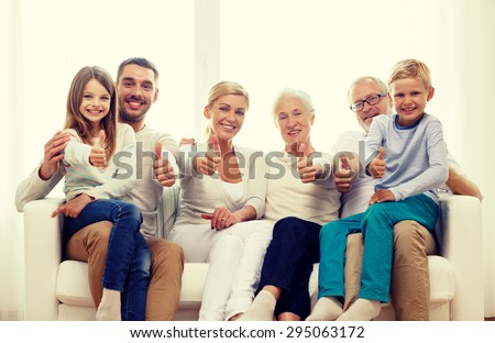 family, happiness, generation and people concept - happy family sitting on couch and showing thumbs up gesture at home
