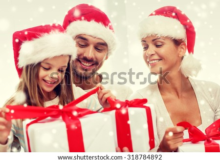 family, happiness, generation, holidays and people concept - happy family in santa helper hats with gift boxes sitting on couch at home - stock photo