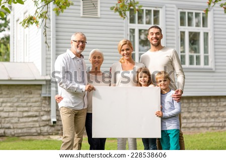 family, happiness, generation, home and people concept - happy family standing in front of house with white blank board outdoors - stock photo