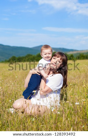 Family - happy mom and her son smiling at nature