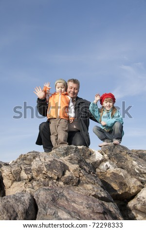 Family have a rest on a grief in the autumn. - stock photo