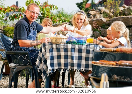 Family having a barbecue in the garden, eating - stock photo