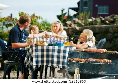 Family having a barbecue in the garden, eating (focus on barbeque grill!) - stock photo