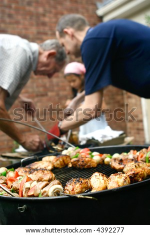 Family having a barbecue in the garden, helping each other out with the food preparation. - stock photo