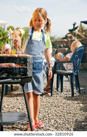 Family having a barbecue party - little kid at the barbecue grill preparing meat and sausages - stock photo