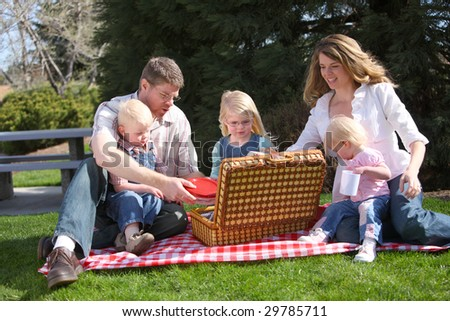 Family having a picnic at the park - stock photo