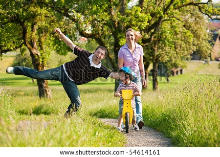Family having a walk outdoors in summer, their little son using a training bike, unspoiled nature - stock photo