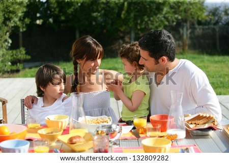 Family having brunch outside on a sunny day - stock photo