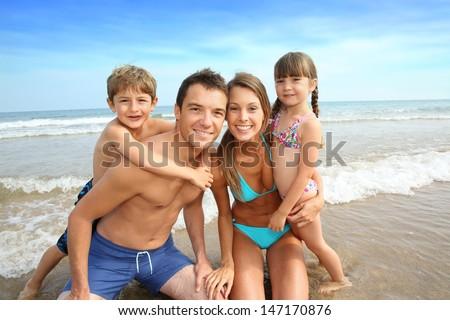Family having fun at the beach - stock photo