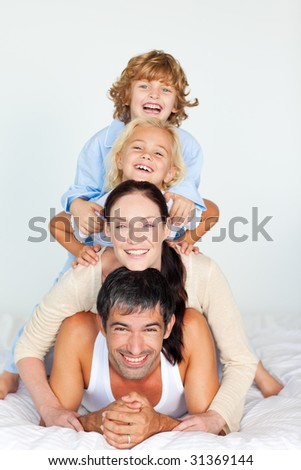Family having fun in bed looking at the camera - stock photo