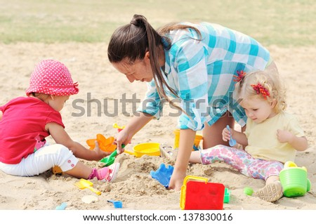 family having fun in sand - stock photo