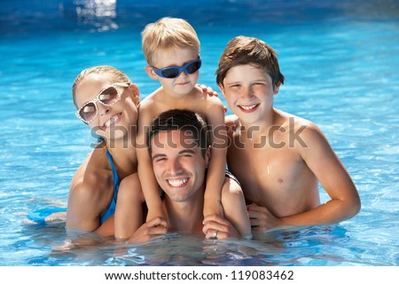 Family Having Fun In Swimming Pool - stock photo