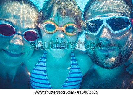Family having fun in swimming pool. Underwater funny portrait. Summer vacation - stock photo