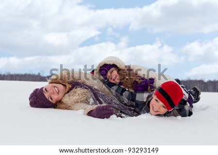 Family having fun in the snow on a winter day - stock photo