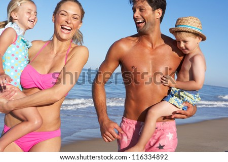 Family Having Fun On Beach - stock photo