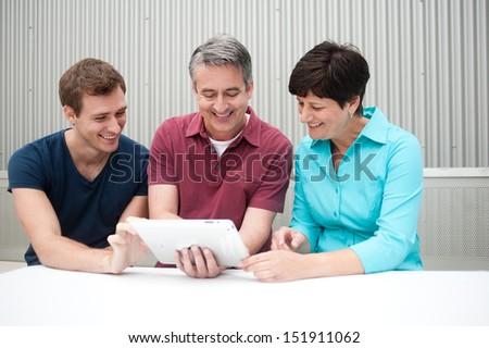 family having fun on tablet - stock photo