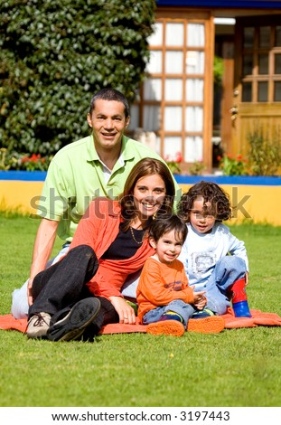 family having fun outdoors in front of their house - stock photo