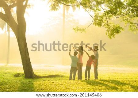 family having fun pointing to somewhere during beautiful sunrise - stock photo