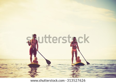 Family Having Fun Stand Up Paddling Together in the Ocean at Sunrise - stock photo