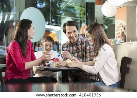Family Having Ice Creams At Table In Parlor - stock photo
