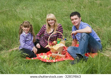 Family having picnic in park. Parents and child on picnic in the forest. Mother, father and daughter relaxing. - stock photo