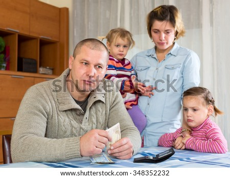 Family having problems with cash. Father is sitting at the table with money in his hands his wife and two sad daughters are sitting behind him - stock photo