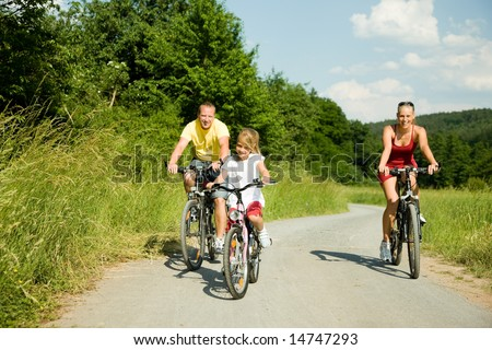 family having riding their bicycles (focus is only on the girl in front!) - stock photo