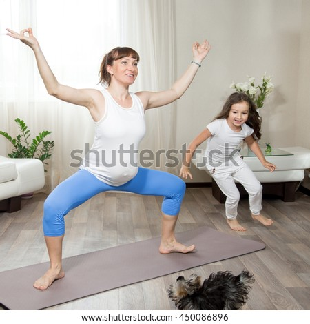 Family healthy lifestyle concept. Pregnancy Yoga and Fitness. Young happy pregnant yoga mom working out in living room interior with her little daughter and pet dog playing and running around at home - stock photo