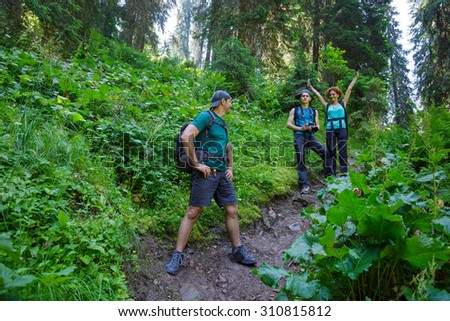 Family hikers walking on a mountain trail through the fir forest - stock photo
