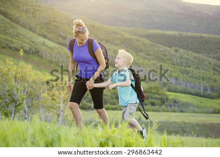 Family hiking in the mountains. A young mother and her son take a hike together in the mountains on a beautiful summer evening. Holding hands and enjoying their time together - stock photo