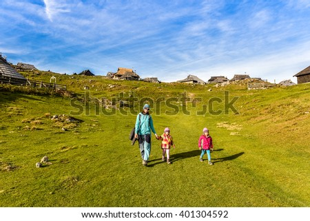 Family hiking in the mountains on idyllic meadow on Velika Planina Slovenia. Mother and two twin children are hiking on the foot path in the nature in alps and hills. Active family . - stock photo